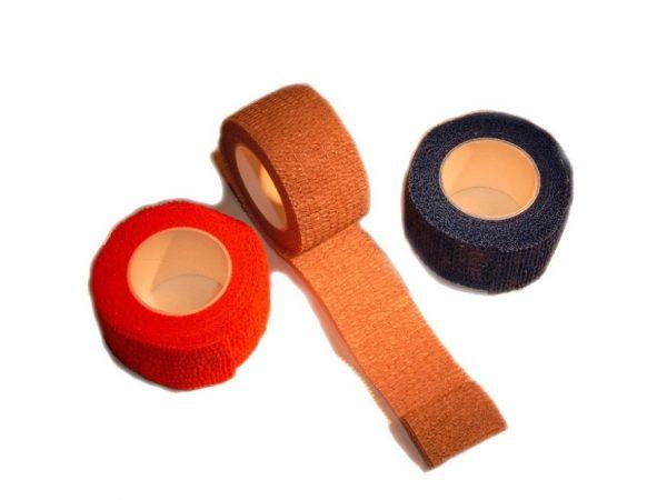 Pflastertape auf Rollen in rot, hautfarben und blau, seitlich und teilweise abgerollt fotografiert