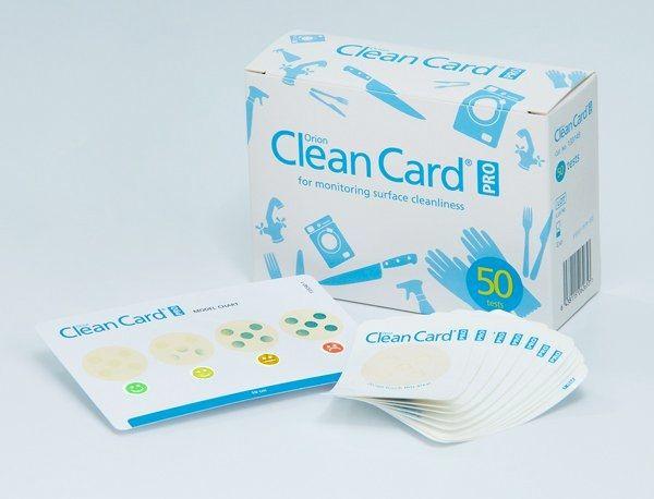 Clean-Card-PRO-Pack-Verpackung mit davorstehendem Inhalt aus Testkarten und Auswertungsraster