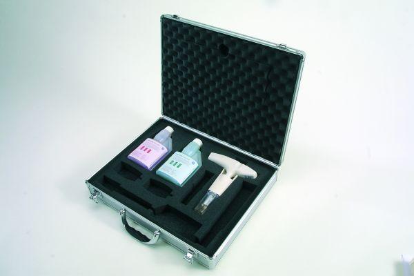 Alukoffer gefüllt mit Messgerät, rosaner und grüner Kalibrierdosierflasche
