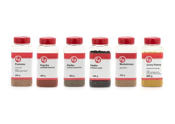 6 aufgereihte Streudosen mit verschiedenen fd Gewürzen wie Pfeffer, Muskatnuss, Paprika und Curry