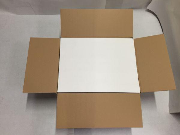 Aufgeklappter Karton mit weißem Einschlagpapier