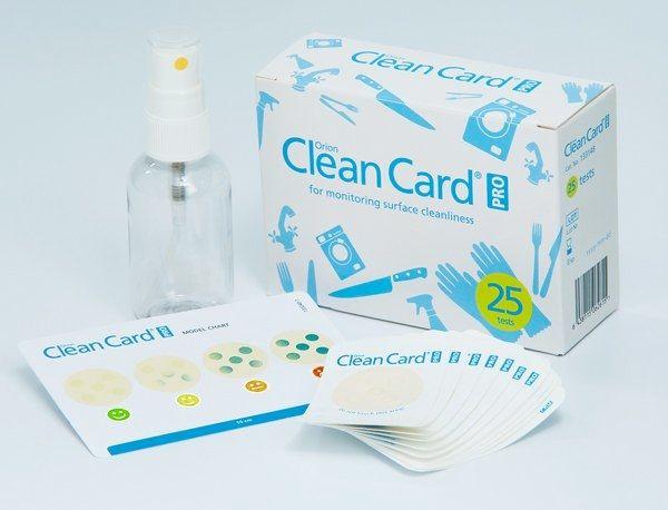 Clean-Card-Kit-Verpackung mit davorstehendem Inhalt aus Testkarten, Sprühdose und Auswertungsraster